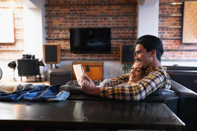 Вид сбоку на молодого человека смешанной расы и молодую кавказку, наслаждающуюся временем дома, сидящую в гостиной, обнимающуюся, улыбающуюся и пользующуюся планшетом. — стоковое фото