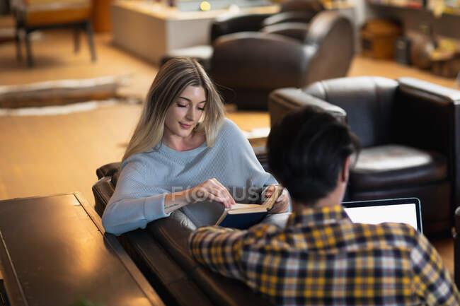 Vue de face d'une jeune femme caucasienne et d'un jeune homme métis appréciant le temps passé à la maison, se reposant dans leur salon, assis sur le canapé, lisant un livre et utilisant un ordinateur portable. — Photo de stock
