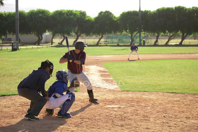 Vue arrière d'un joueur de baseball masculin caucasien lors d'un match de baseball par une journée ensoleillée, se préparant à frapper une balle avec une batte de baseball, un receveur et un autre joueur sont accroupi derrière un frappeur — Photo de stock