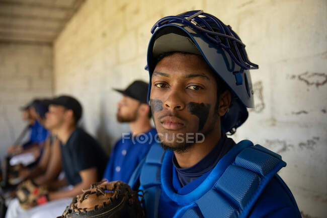 Portrait of a mixed race male baseball player, preparing before a game, wearing a team uniform, a helmet and chest pads, sitting in a changing room, looking at a camera, with his teammates in the background — Stock Photo