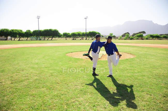Vue latérale d'un joueur de baseball de race blanche et d'un joueur de baseball de race mixte appuyés les uns sur les autres, debout sur une jambe, tenant et étirant l'autre jambe, lors d'une séance d'entraînement sur un terrain de jeu par une journée ensoleillée — Photo de stock