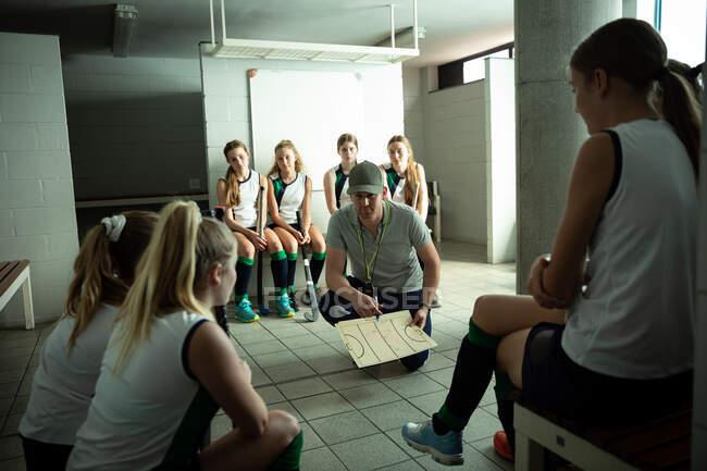 Первый взгляд на кавказского тренера по хоккею на траве, взаимодействующего с группой кавказских хоккеистов, сидящего в раздевалке и показывающего им план игры — стоковое фото