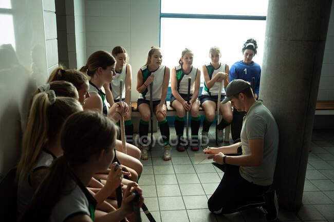 Side view of a Caucasian male field hockey coach interacting with a group of female Caucasian field hockey players, sitting in a changing room, showing them a game plan — Stock Photo
