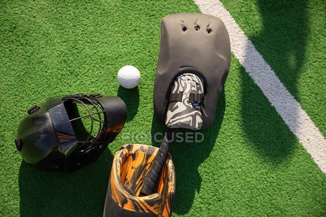 Крупный план хоккейного снаряжения, шлема и мяча, лежащих на хоккейном поле в солнечный день — стоковое фото