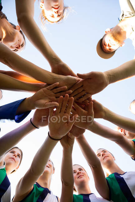 Low angle close up of a group of female Caucasian field hockey players and their Caucasian male coach, preparing before a game, huddling, hands stacking, on a sunny day — Stock Photo