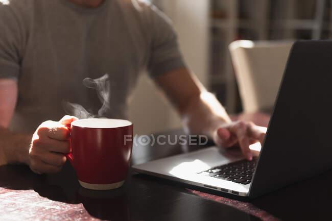 Vista laterale metà sezione di uomo trascorrere del tempo a casa, seduto vicino alla scrivania, utilizzando il computer portatile e tenendo una tazza di bevanda calda. — Foto stock