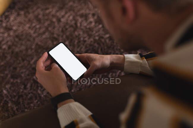 Vista aerea di un giovane caucasico che trascorre del tempo a casa, sdraiato su un divano e usando il suo smartphone. — Foto stock