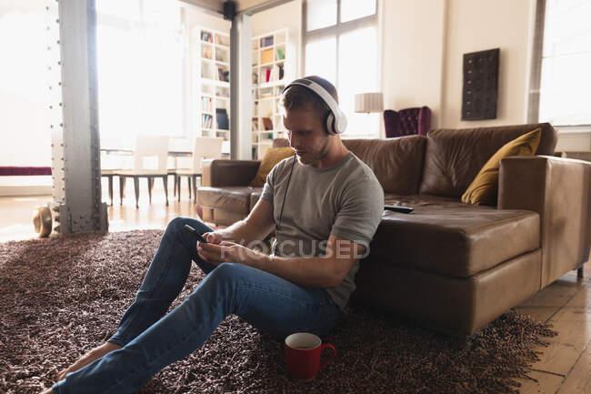На вигляд молодий кавказький чоловік у навушниках проводить час удома, лежачи на килимі і користуючись смартфоном.. — стокове фото