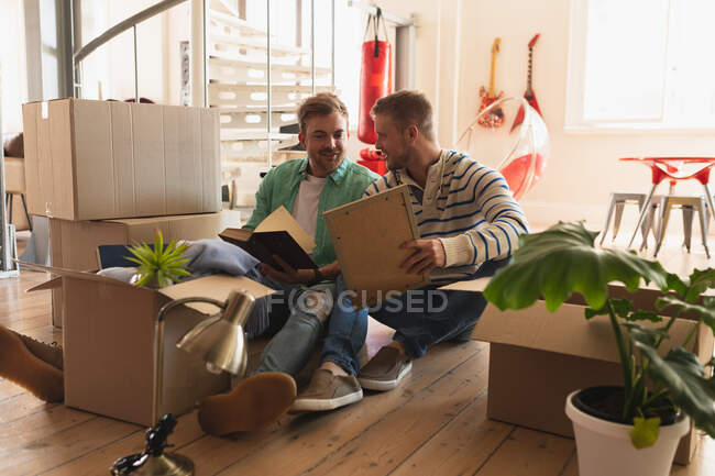 Front view of a Caucasian male couple moving in to a new apartment, sitting on the floor with cardboard boxes and interacting — Stock Photo