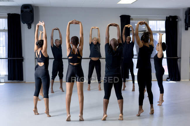 Rear view of a multi-ethnic group of fit male and female modern dancers wearing black outfits practicing a dance routine during a dance class in a bright studio, creating a circle and stretching up keeping hands above their heads. — Stock Photo