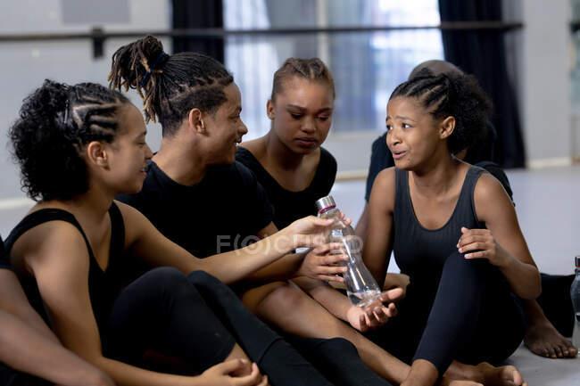 Вид сбоку на многонациональную группу современных танцоров мужского и женского пола в черных нарядах, практикующих танцевальную рутину во время занятий в яркой студии, наслаждающихся отдыхом, сидящих на полу, взаимодействующих и пьющих воду. — стоковое фото