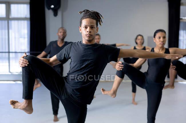 Вид спереди на танцующего мужчину смешанной расы в черной одежде, стоящего перед многоэтничной группой танцующих мужчин и женщин, держа ногу и протягивая руку. — стоковое фото