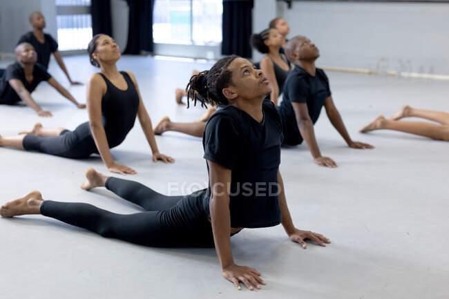 Вид сбоку на многонациональную группу современных танцоров мужского и женского пола в черных нарядах, практикующих танцевальную рутину во время занятий танцами в яркой студии, лежащих на полу и растянувшихся. — стоковое фото