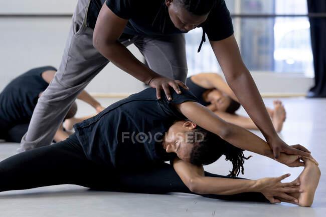 Вид сбоку на двух современных танцоров смешанной расы, одетых в черные костюмы, практикующих танцевальную программу во время урока танцев в яркой студии, поддерживающих друг друга во время растяжки, с другими танцорами, тренирующимися на заднем плане. — стоковое фото