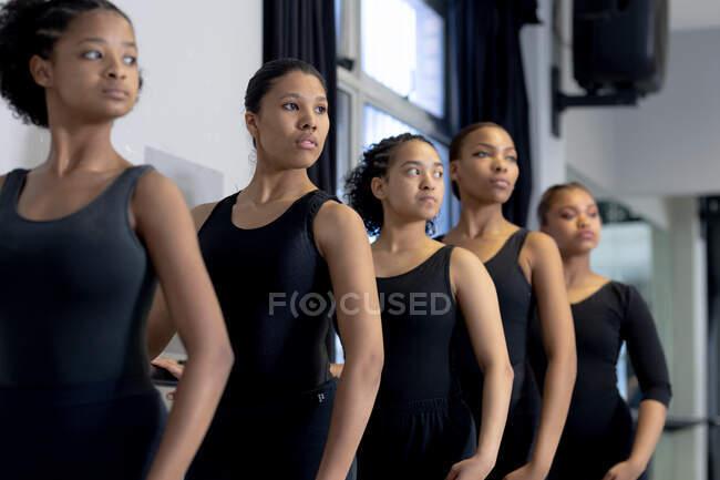 Seitliche Nahaufnahme einer multiethnischen Gruppe fitter moderner Tänzerinnen in schwarzen Outfits, die während eines Tanzkurses in einem hellen Studio an einem Geländer stehen und die Arme auf den Hüften haben. — Stockfoto