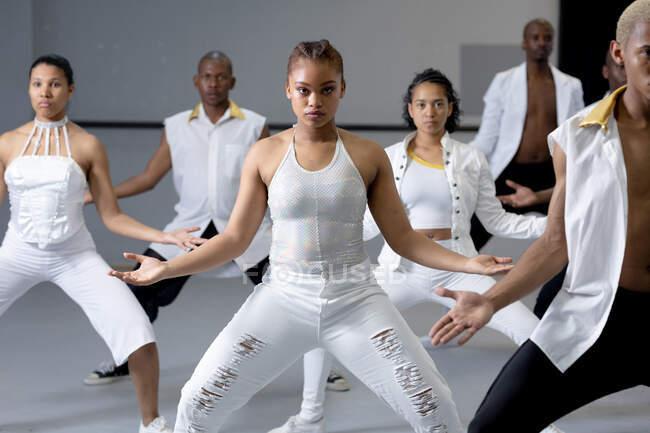 Veduta frontale di un gruppo multietnico di ballerini moderni maschili e femminili in forma che indossano abiti bianchi che praticano una routine di danza durante una lezione di danza in uno studio luminoso. — Foto stock