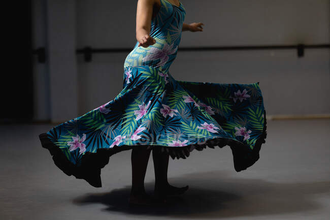 Side view mid section of female dancer wearing blue floral dress, dancing in a studio and looking straight into a camera. — Stock Photo