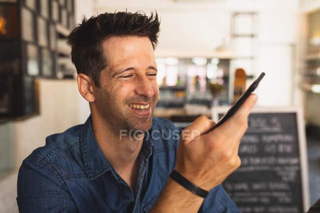 Vista frontale da vicino di un uomo caucasico che indossa abiti casual, seduto accanto a un tavolo in una caffetteria, sorridente e usando il suo smartphone — Foto stock