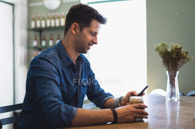 Side view of a Caucasian man wearing casual clothes, sitting by a table in a coffee shop, holding a glass of coffee and using his smartphone — Stock Photo