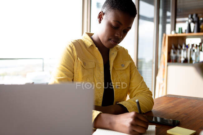 Front view of an African American woman sitting in her living room in front of a window on a sunny day, writing in a notebook — Stock Photo