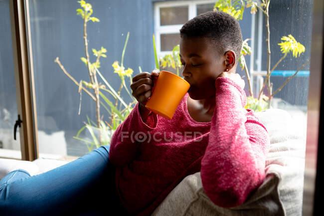 Vista lateral de una mujer afroamericana sentada en su sala de estar frente a una ventana en un día soleado, sosteniendo una taza y bebiendo - foto de stock