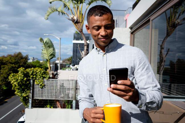 На перший погляд афроамериканець, що висів на балконі в сонячний день, користуючись смартфоном і тримаючи чашку. — стокове фото