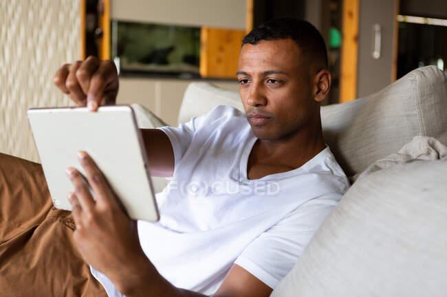 Зворотний вид афроамериканського чоловіка, який висів у своїй вітальні, сидячи на дивані, за допомогою ноутбука. — стокове фото