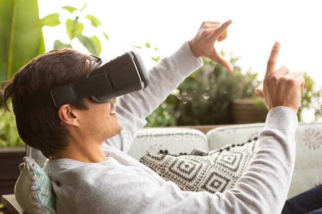 Side view close up of a Caucasian man hanging out on a balcony on a sunny day, wearing VR goggles, pointing to a virtual screen — Stock Photo