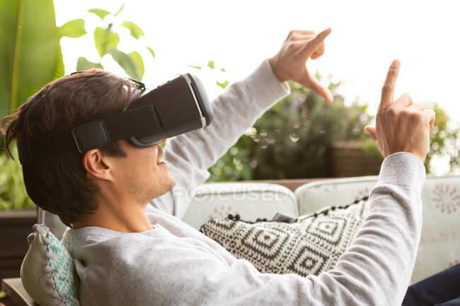 Вигляд збоку біля кавказького чоловіка, який висів на балконі в сонячний день, одягнений в VR окуляри, вказуючи на віртуальний екран — стокове фото