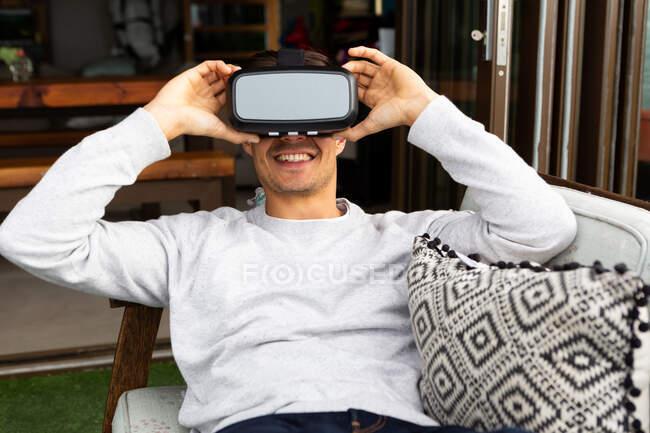 Vista frontal close-up de um homem caucasiano pendurado em uma varanda em um dia ensolarado, vestindo óculos VR e sorrindo — Fotografia de Stock