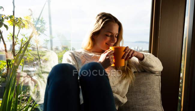 Vista frontale di una donna caucasica seduta nel suo salotto di fronte a una finestra in una giornata di sole, con una tazza e un sorriso — Foto stock