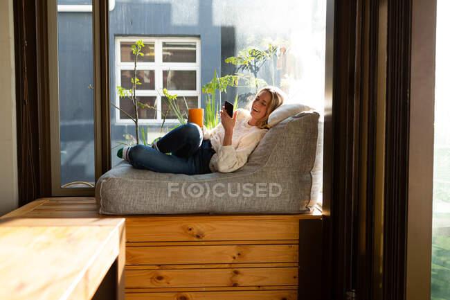 Вид сбоку на кавказку, сидящую в гостиной перед окном в солнечный день, используя смартфон, держа кружку и улыбаясь — стоковое фото