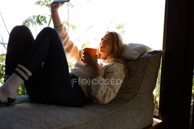 Вид сбоку на кавказку, сидящую в гостиной перед окном в солнечный день, делающую селфи и держащую кружку — стоковое фото