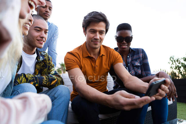 Front view of a multi-ethnic group of friends hanging out on a roof terrace on a sunny day, using a smartphone and smiling — Stock Photo