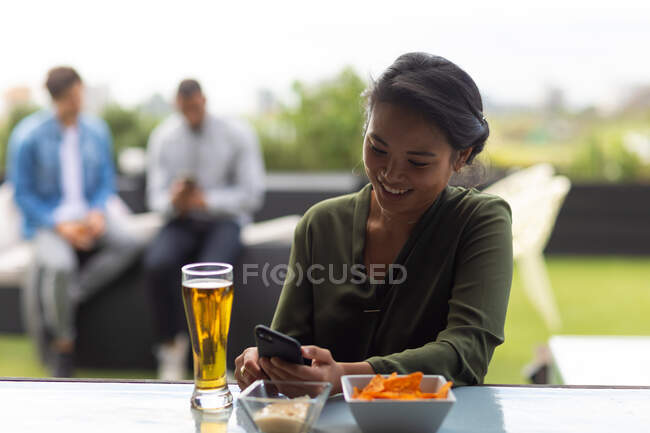 Front view of an Asian woman hanging out on a roof terrace on a sunny day, using a smartphone, smiling, a glass of beer beside her on a table, with people talking in the background — Stock Photo