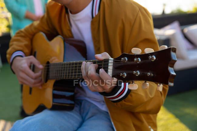 Frontansicht mittlerer Abschnitt eines Mannes, der an einem sonnigen Tag auf einer Dachterrasse sitzt und Gitarre spielt — Stockfoto