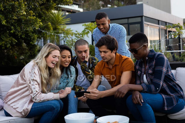 Front view of a multi-ethnic group of friends hanging out on a roof terrace, sitting on a sofa, using a smartphone and smiling — Stock Photo