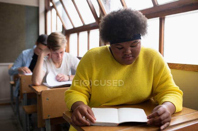 Vue de face d'une adolescente afro-américaine dans une classe d'école assise au bureau, se concentrant et lisant, avec des camarades de classe masculins adolescents assis à des bureaux travaillant en arrière-plan — Photo de stock