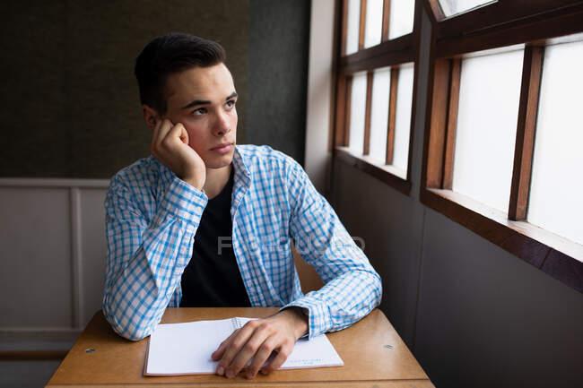 Вид сбоку на мальчика-белого подростка в школьном классе, сидящего за столом, сосредоточенного, смотрящего в окно и склоняющего голову на руку — стоковое фото