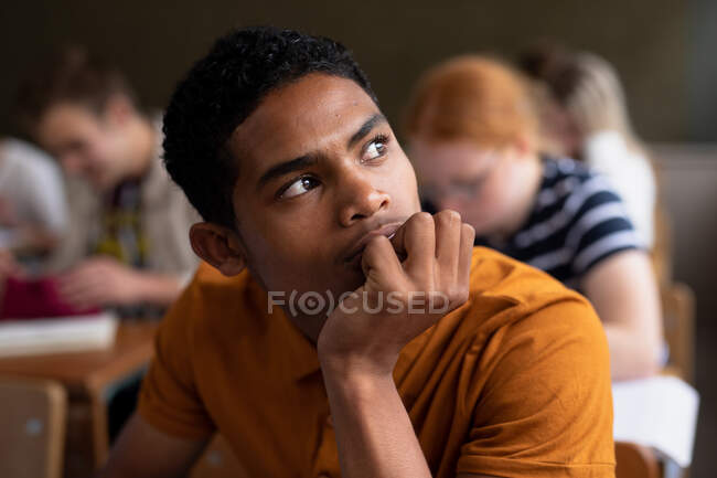Side view close up of a teenage mixed-race boy in a school classroom sitting at desk, concentrating, with teenage male and female classmates sitting at desks working in the background — Stock Photo