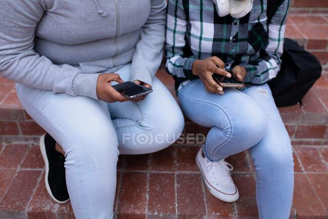 Vue de face de la section basse près de deux lycéennes adolescentes, à l'aide de smartphones et assises sur des marches dans le terrain de l'école — Photo de stock