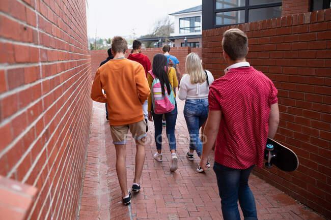 Vista posteriore di un gruppo multietnico di alunni adolescenti di sesso maschile e femminile con schoolbag appendere fuori, a piedi nel loro liceo, uno che trasporta uno skateboard — Foto stock