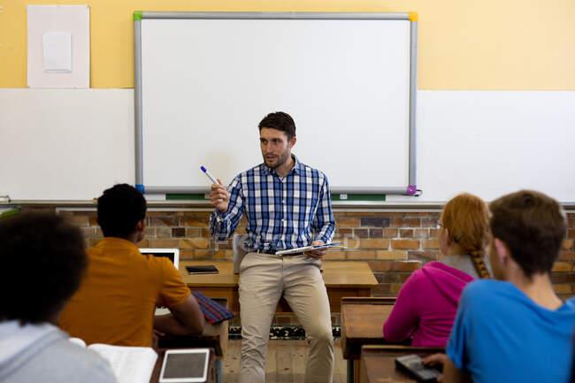 Vorderansicht eines männlichen kaukasischen Lehrers, der ein Tablet in der Hand hält und mit einer multiethnischen Gruppe von Teenagern in einem Klassenzimmer der High School spricht, die an Schreibtischen sitzt und zuhört — Stockfoto