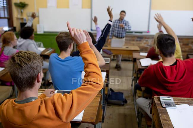 Вид сзади на многонациональную группу школьников-подростков в классе школы, сидящих за партами, все поднимающие руки, чтобы ответить на вопрос, их учитель-мужчина, стоящий на заднем плане — стоковое фото
