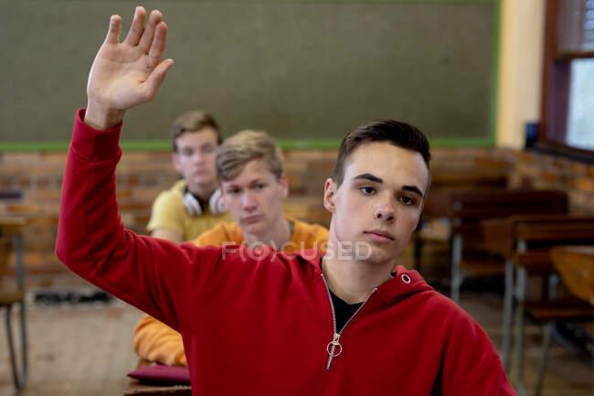 Vista frontal de un adolescente caucásico en una clase de secundaria sentado en el escritorio, levantando la mano para responder a una pregunta, con compañeros de clase adolescentes sentados en escritorios trabajando en el fondo — Stock Photo