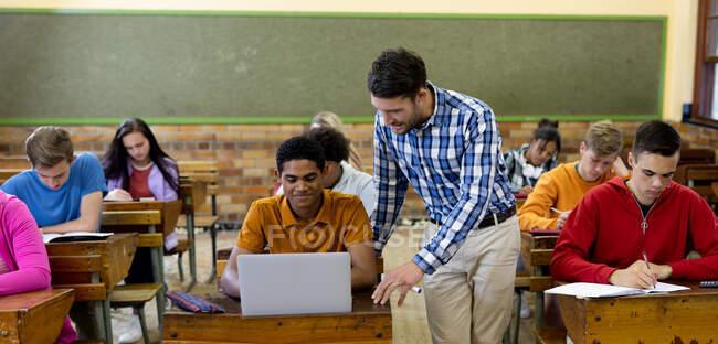 Vue de face d'un enseignant caucasien debout et parlant à un adolescent de race mixte assis à son bureau à l'aide d'un ordinateur portable dans une salle de classe du secondaire, avec ses camarades de classe multiethniques masculins et féminins assis à des bureaux travaillant autour de lui — Photo de stock