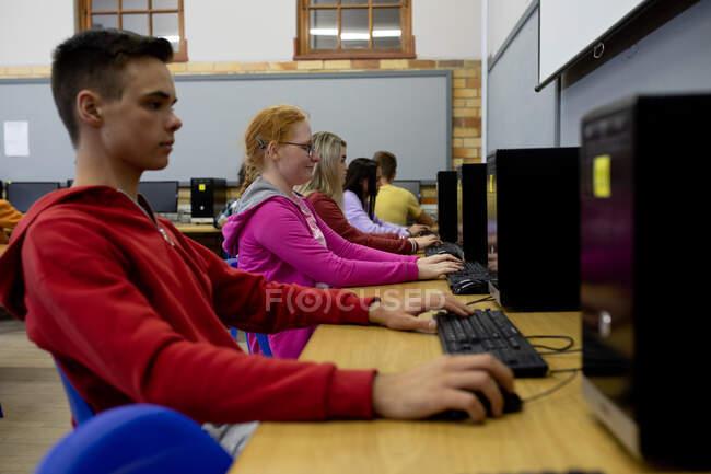 Vista lateral de un grupo multiétnico de adolescentes de secundaria alumnos de escuelas masculinas y femeninas en un aula, trabajando en computadoras y concentrándose - foto de stock