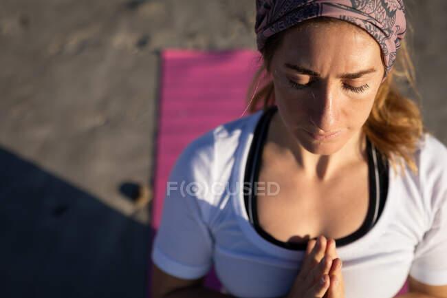 Высокий угол крупным планом кавказской женщины в белой рубашке на солнечном пляже, медитирующей, практикующей йогу с закрытыми глазами и руками в молитвенном положении. — стоковое фото