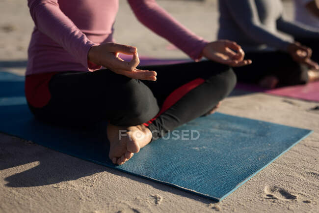 Вид сбоку на середину группы подруг, наслаждающихся упражнениями на пляже в солнечный день, практикующих йогу сидя в позе йоги, посредничающих в позе лотоса. — стоковое фото