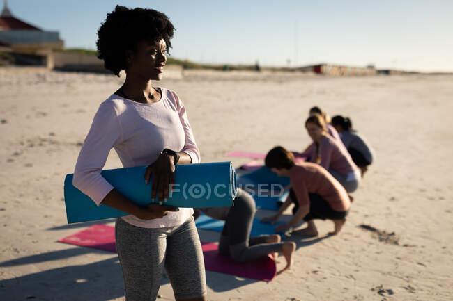 Вид сбоку на афроамериканку, одетую в спортивную одежду, держащую синий коврик для йоги под мышкой, стоящую на солнечном пляже с друзьями на коленях на заднем плане. — стоковое фото